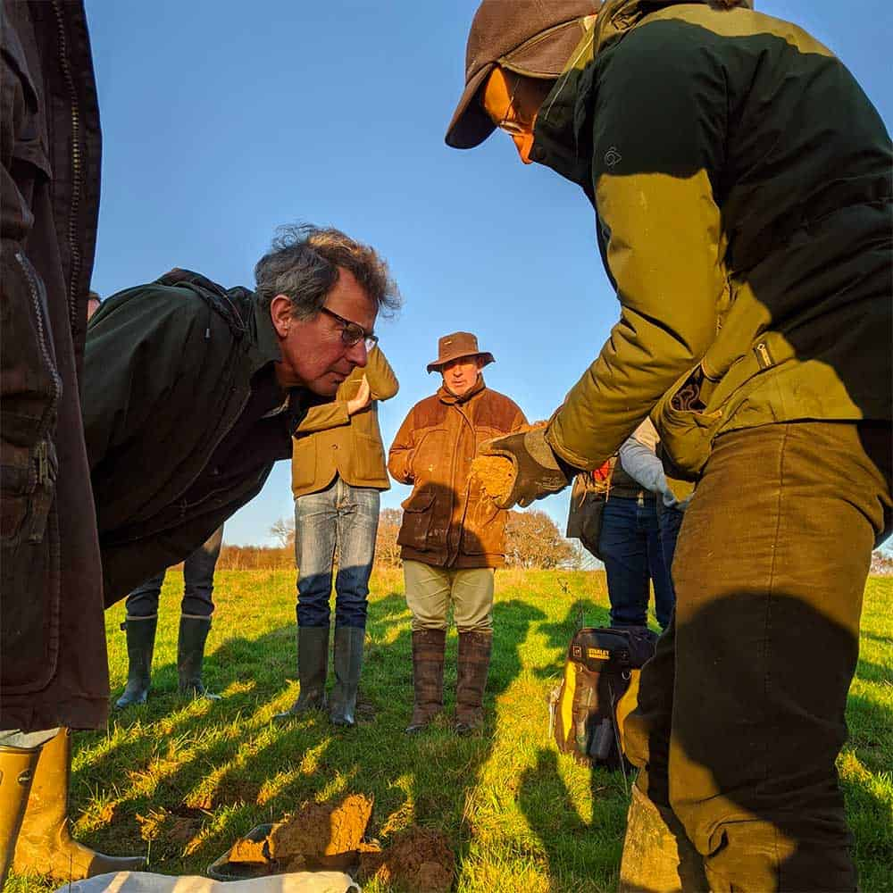 Niels and farmers looking at soil sample